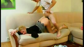 Venäläinen tyttö koruja kaulassa hänen kaunis eroottinen hieronta video poikansa sohvalla.